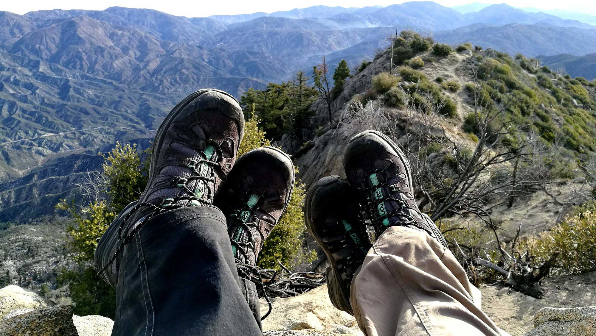 Feet and mountain view of people relaxing on top of mountain